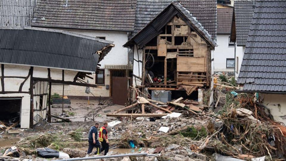 Rheinland-Pfalz, Schuld: Zwei Feuerwehrleute gehen in dem Dorf im Kreis Ahrweiler nach dem Unwetter mit Hochwasser durch den Schutt. Mindestens sechs Häuser wurden durch die Fluten zerstört.