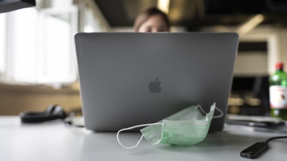 Eine Frau arbeitet am Arbeitsplatz im Büro, ihre Schutzmaske liegt auf dem Tisch (Symbolbild).