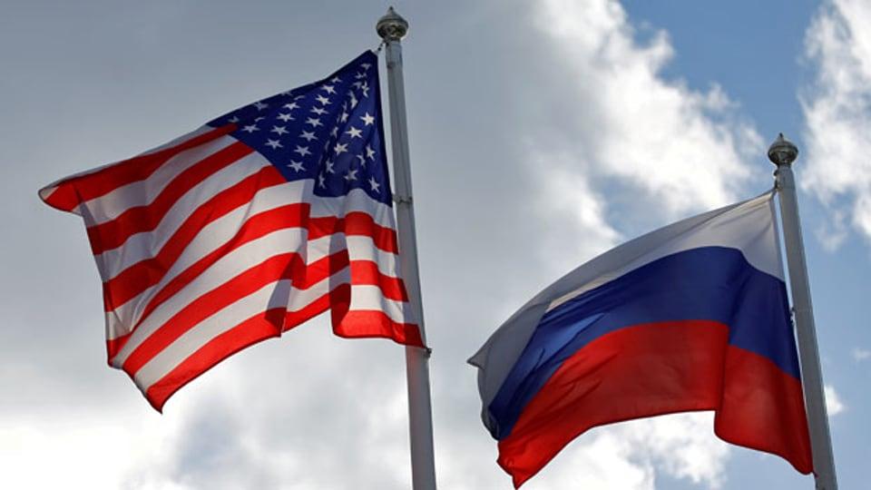 Russische und US-Staatsflaggen wehen im Wind.