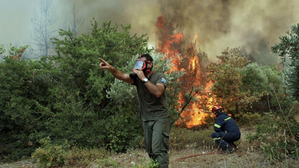 Feuerwehrleute versuchen, im Dorf Avgaria auf der Insel Euböa, ein Feuer zu löschen. Griechenland, August 2021.