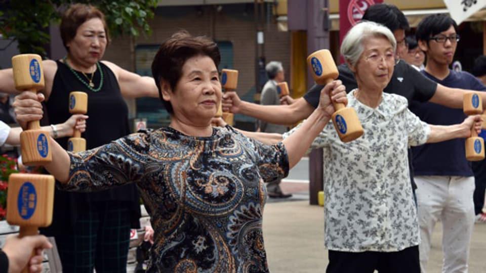 Ältere Menschen trainieren mit hölzernen Hanteln auf dem Gelände eines Tempels in Tokio.