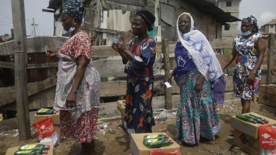 In der nigerianischen Grossstadt Lagos warten Bewohnerinnen auf Lebensmittelspenden.