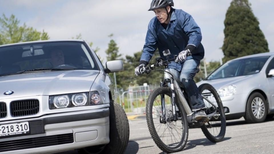 Mann fährt auf E-Bike, nebenan steht ein Auto.