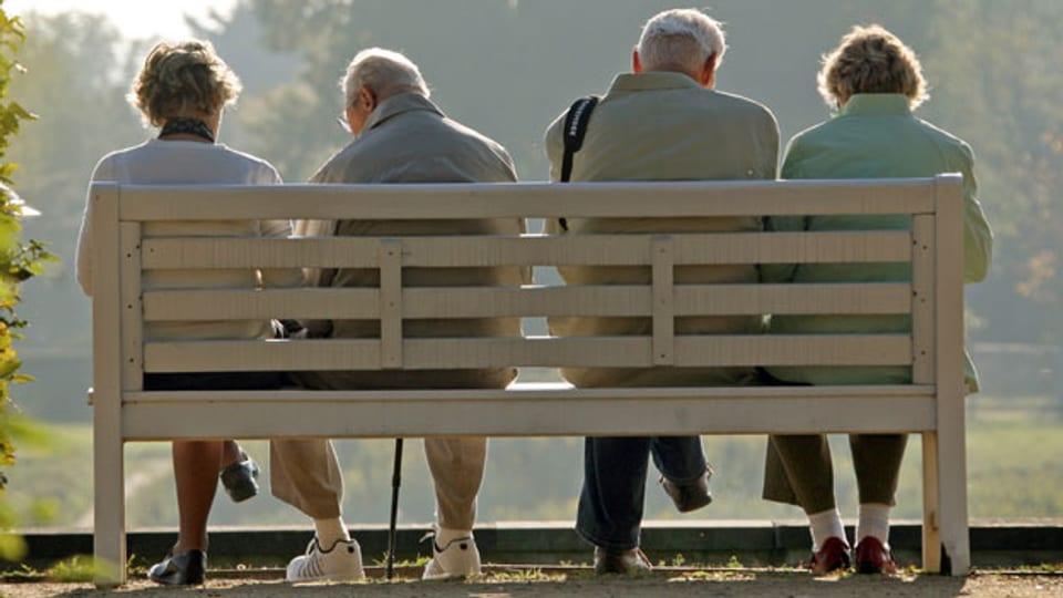 Rentner sitzen auf einer Bank im Park.