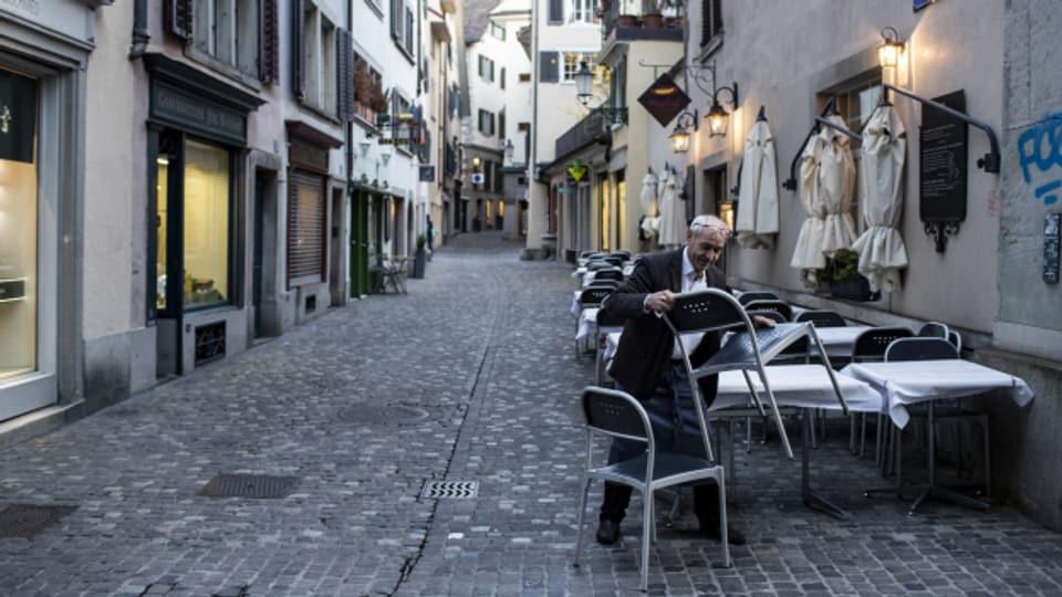 «Restaurant geschlossen»: Der Zürcher Wirt Jorge stellt am Montagabend die Gartenstühle seines Restaurants zusammen.