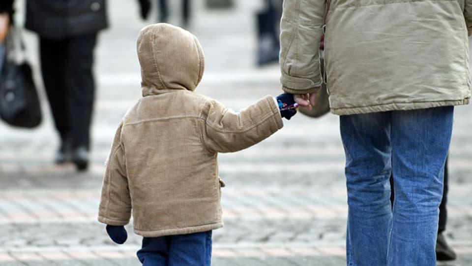 Kind an der Hand des Vaters. Symbolbild.