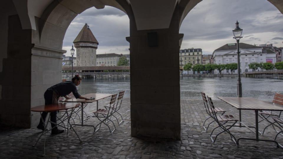 Eine Mitarbeiterin wischt Tische auf einer Restaurantterrasse