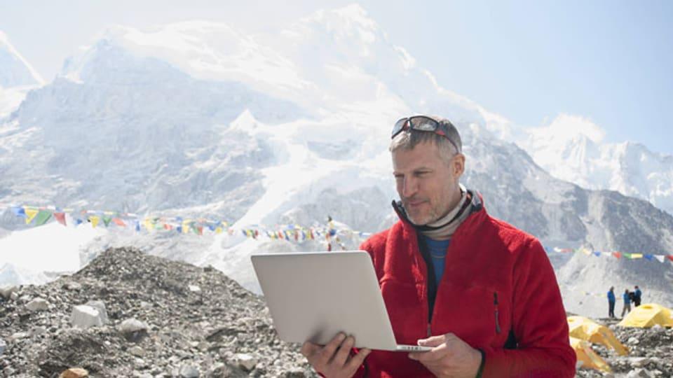 Symbolbild. Ein Mann arbeitet an seinem Laptop in den Bergen.