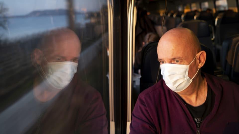 Ein Pendler im Zug mit Maske im März 2021.