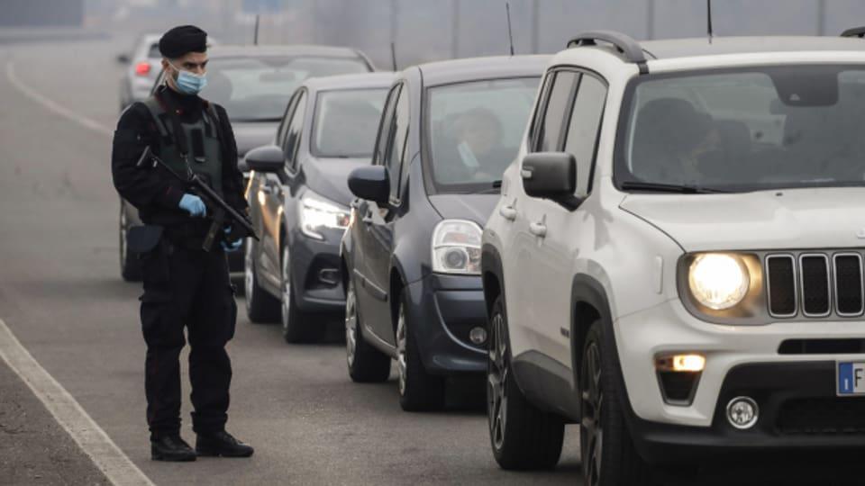 Italienische Polizisten kontrollieren Autofahrende auf der Autobahn