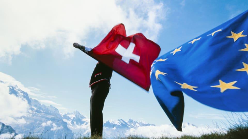 Ein Fahnenschwinger schwingt die Schweizer und EU Flagge