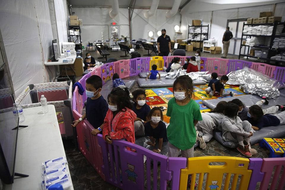Kinder in einem Flüchtlingslager spielen in einer Lagerhalle und schauen fern