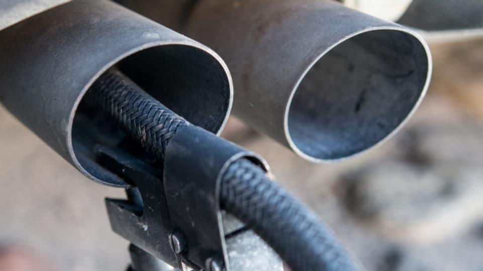 Ein Messschlauch eines Gerätes zur Abgasuntersuchung für Dieselmotoren steckt in einem Auspuffrohr.