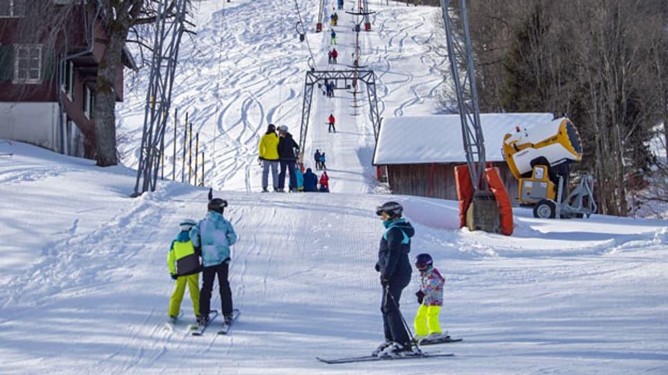 Skifahrer auf dem Bügellift bei schönem Winterwetter und guten Pistenverhältnissen. Februar 2020 im Sörenberg.
