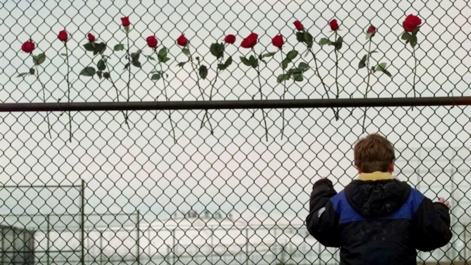 13 Rosen hängen an einem Zaun der Columbine High School, wenige Tage nach dem Amoklauf im April 1999.