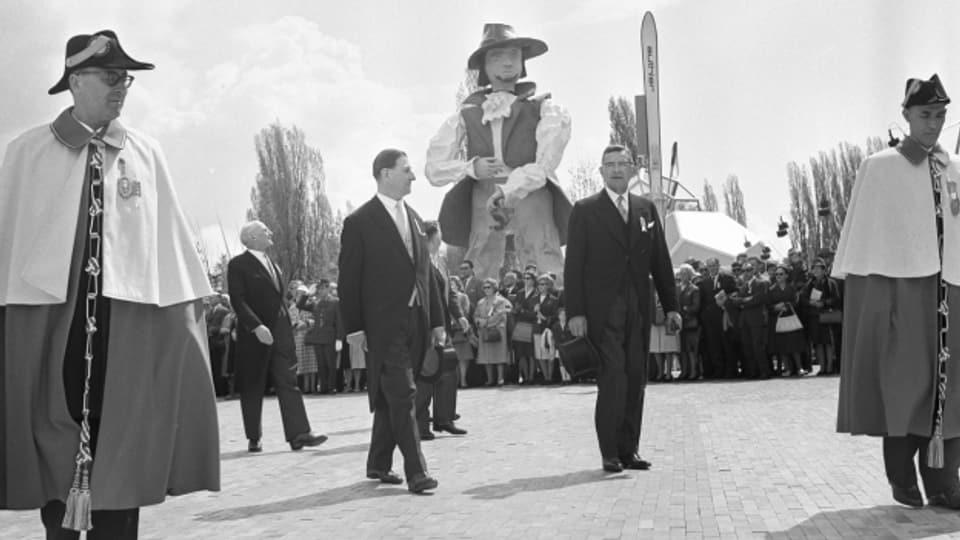 Bundesräte und Bundesweibel an der Eröffnung der Expo 64, mit dem Riesen Gulliver im Hintergrund.