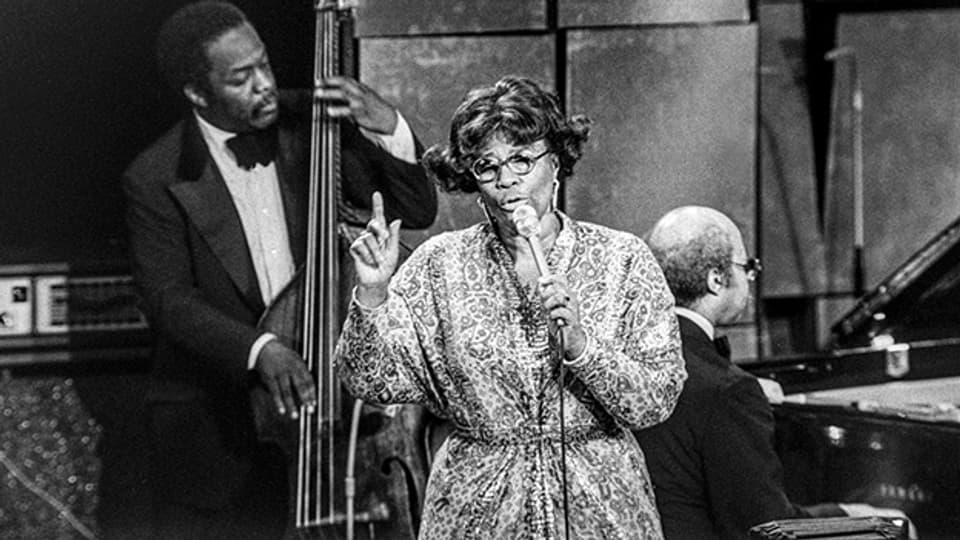 Die amerikanische Jazzsängerin Ella Fitzgerald (1917-1996) im Juli 1975 zusammen mit Keter Betts (Bass) und Tommy Flanagan (Klavier) am Montreux Jazz Festival.