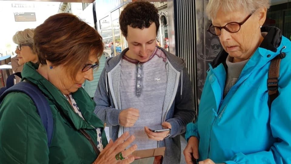 Kursteilnehmerinnen starten mithilfe des Kursleiters die Fairtig-App vor der Probefahrt mit dem Tram.