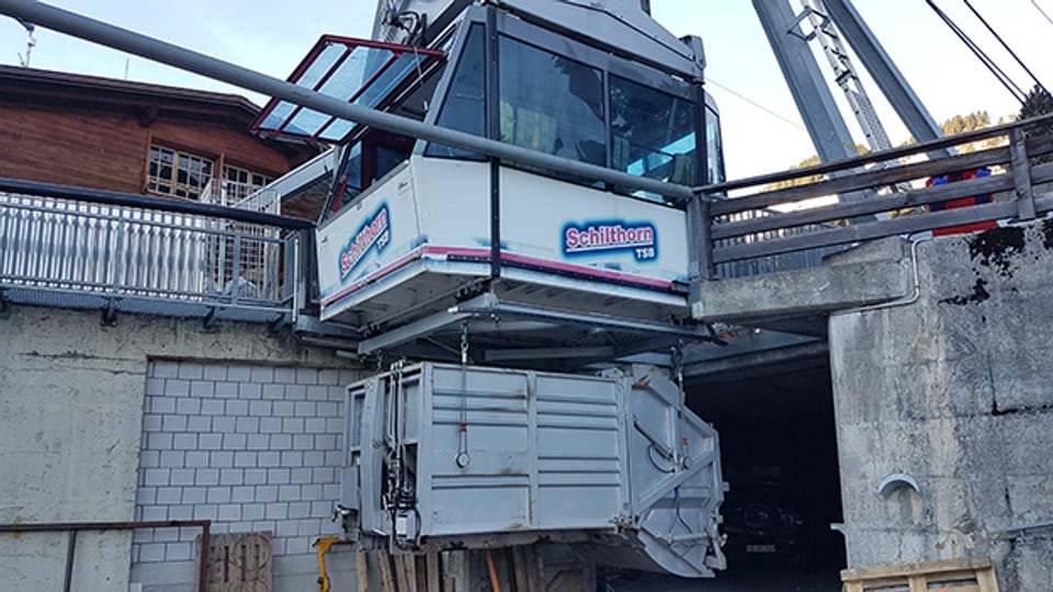 Der Container des Müllwagens wird unten an der Gondel der Transportbahn befestigt.