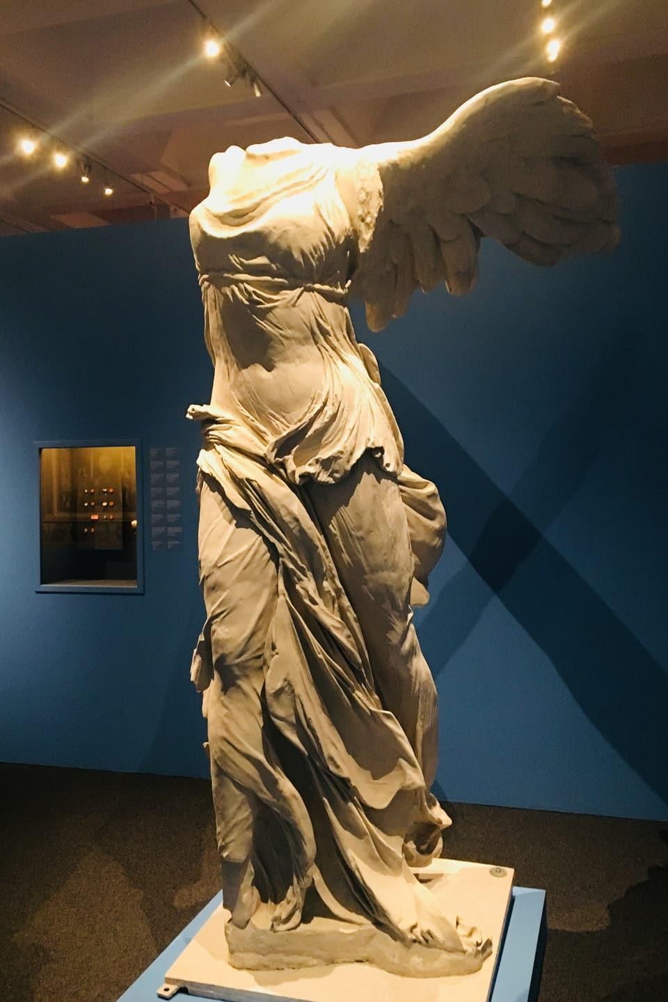 statua feminina cun alas, dentant senza chau.