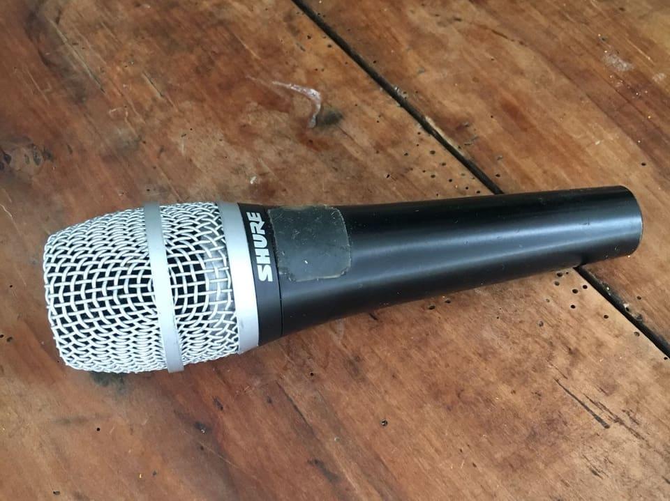 Glänzendes Mikrofon auf wunderbar nussbraunem Holz liegend