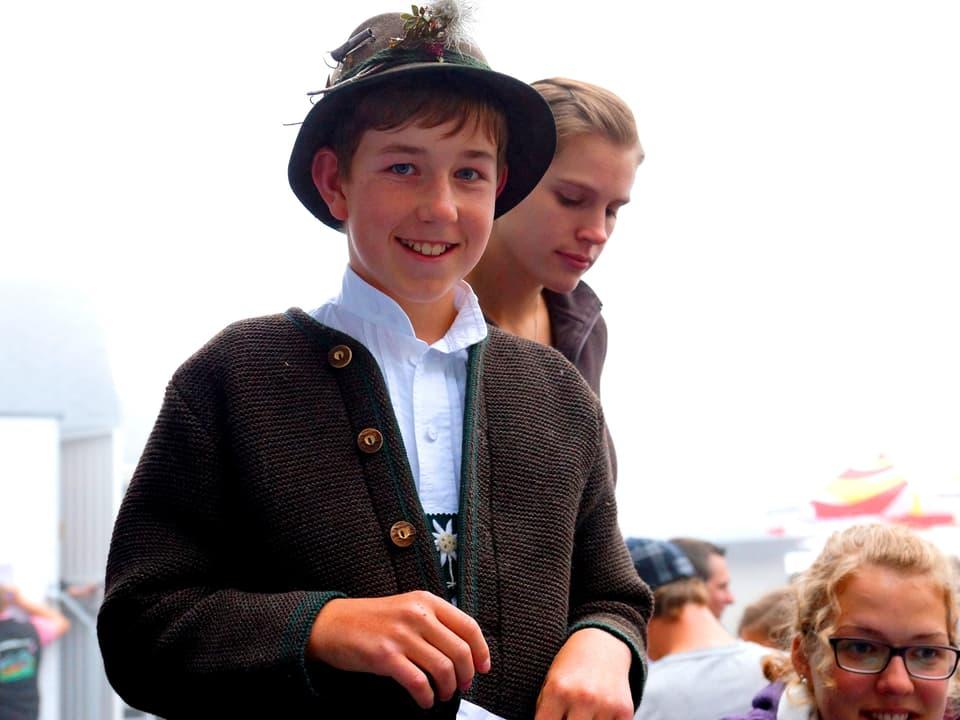 Ein Bub mit Hut und gestrickter Weste.