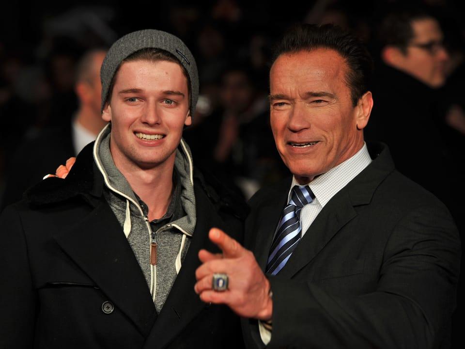 Partrick und Arnold Schwarzenegger in die Kamera blickend.