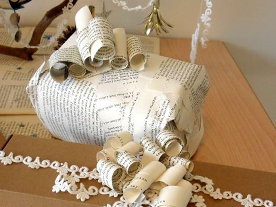 Geschenk in Zeitungspapier verpackt mit Verzierungen.