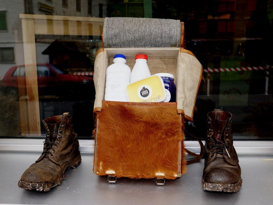 Ein Ledertasche mit Milchbehältern, daneben je ein Bergschuh.