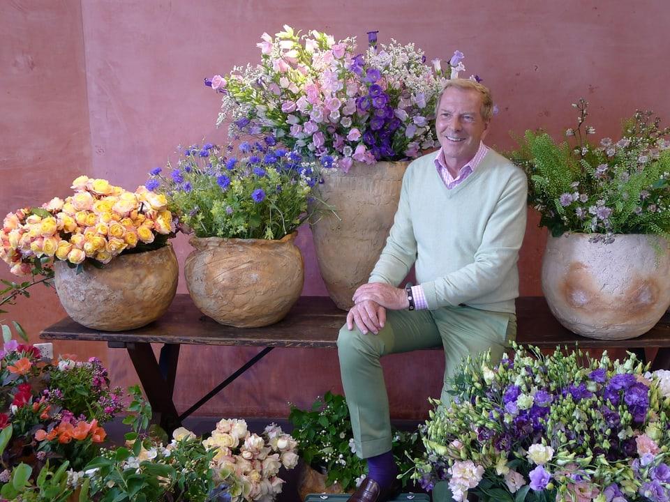 Kurt Aeschbacher sitzt auf einer Holzbank. Darauf sind erdfarbene Tontöpfe mit Schnittblumen arrangiert. Im einen Topf gelbe Rosen. Blaue, lila, zartrosa farbene Blüten zieren die anderen Gefässe. Im Vordergrund weitere Schnittblumen. Kurt Aeschbacher sitzt quasi in einem Blütenmeer.