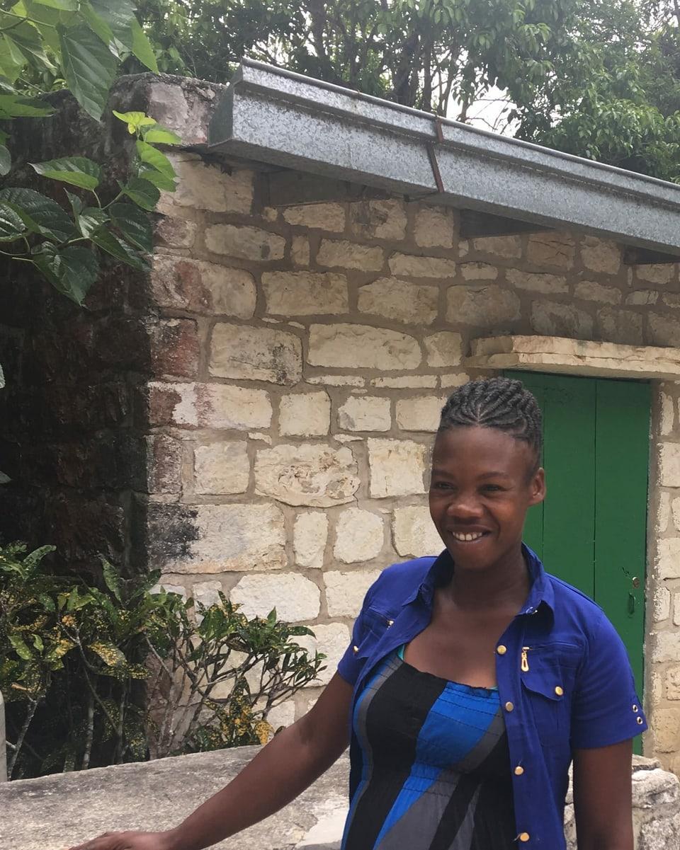 Eine schwangere Frau steht vor einem Haus.