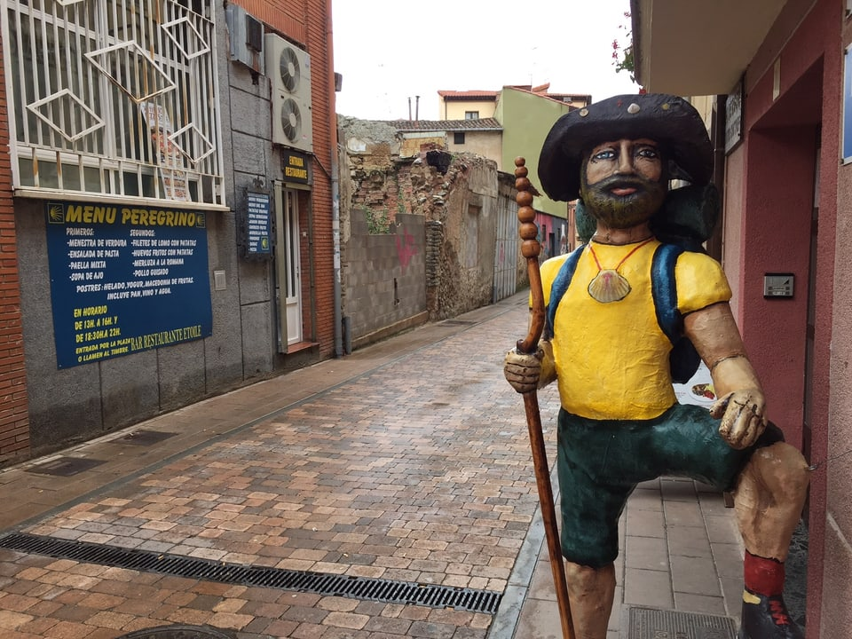 Pilgerstatue aus Holz steht am Strassenrand
