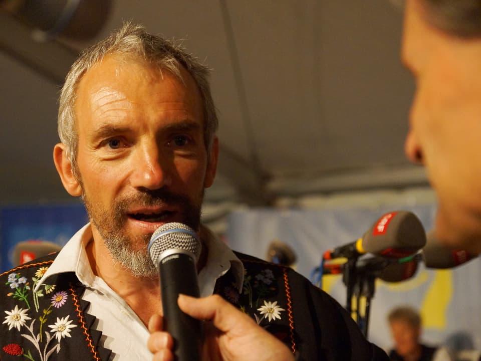 Franz Müller in einer Sennenkutte sagt etwas ins Mikrofon.