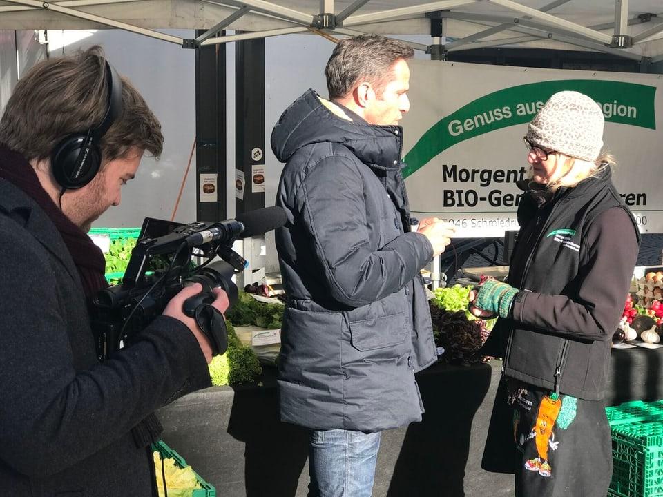 Adrian Küpfer an einem Marktstand mit Gemüse. Er unterhält sich mit einer Frau.