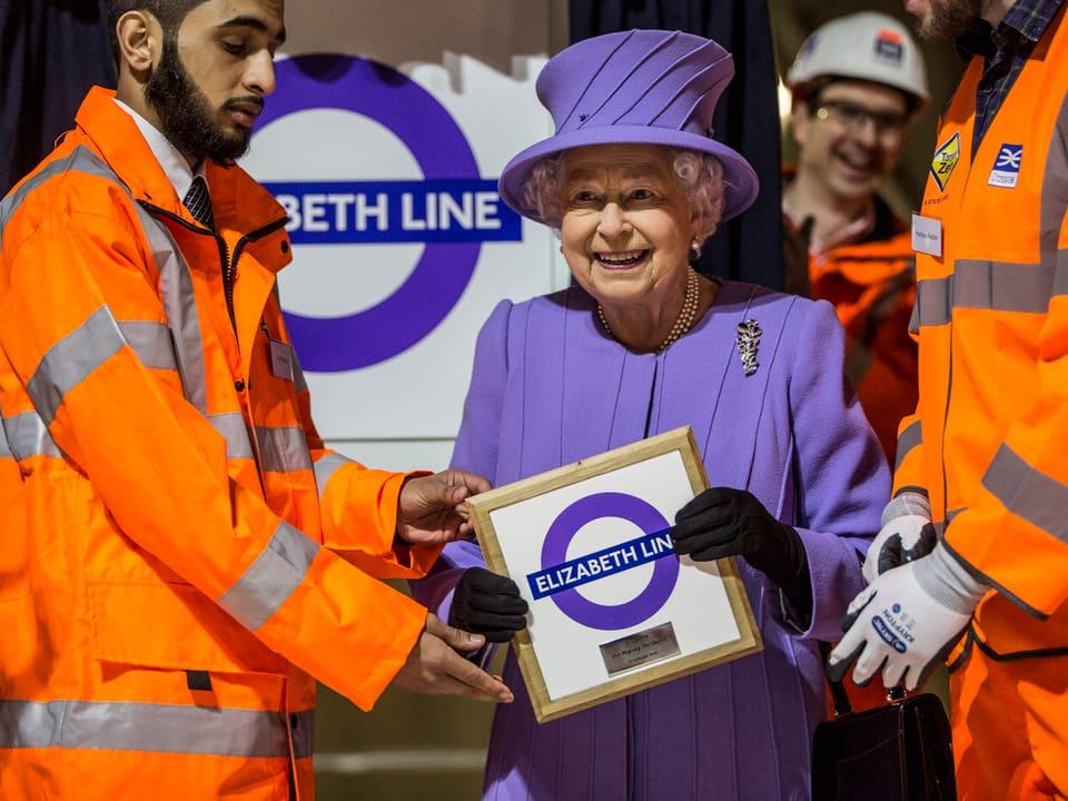Die Queen ein Bild in der Hand haltend und lächelnd.