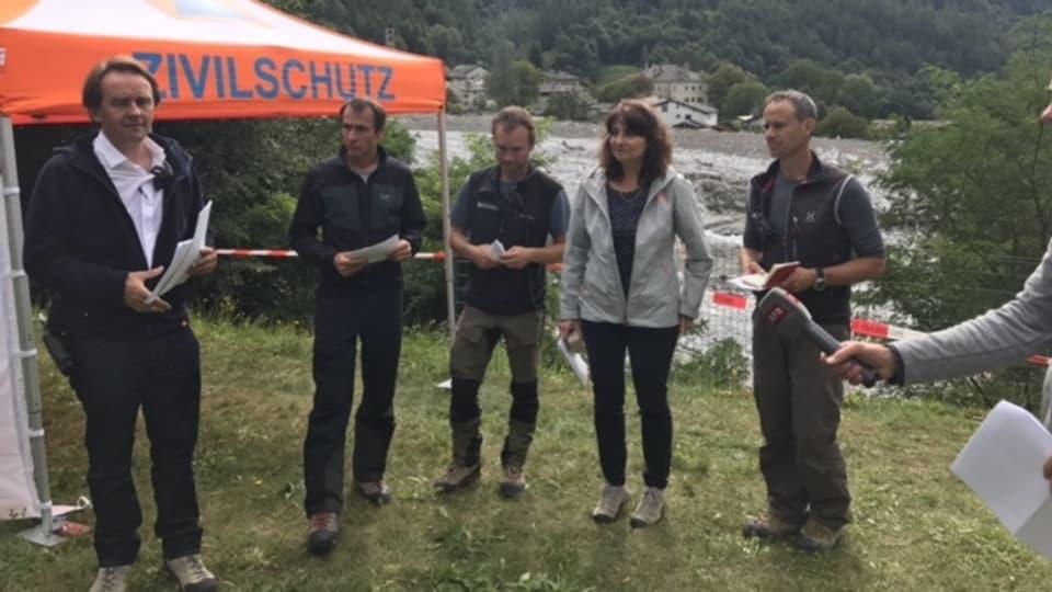 Christian Gartmann - il pledader da la vischnanca davant ina tenda da la protecziun civila cun auters responsabels ed Anna Giacometti durant ina conferenza da pressa.