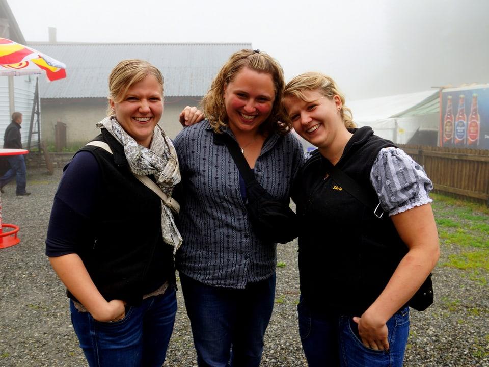 Die Umgebung ist vom Nebel umhangen, aber die drei Frauen lachen sonnig in die Kamera.