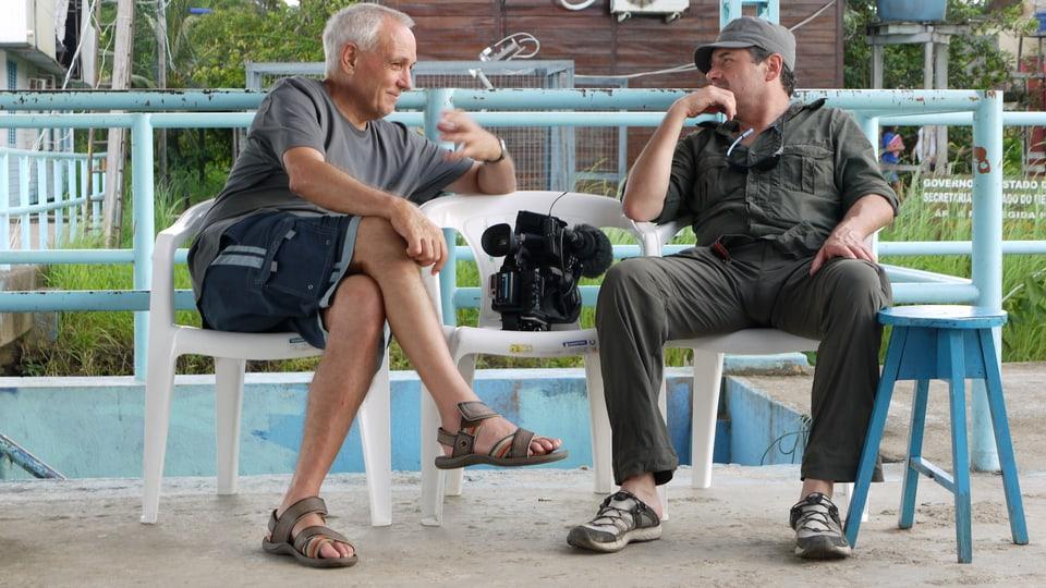 Übersetzer Ruedi Leuthold erzählt während der Drehpause am Pier Kameramann Laurent Stoop vom Amazonas-Delta.