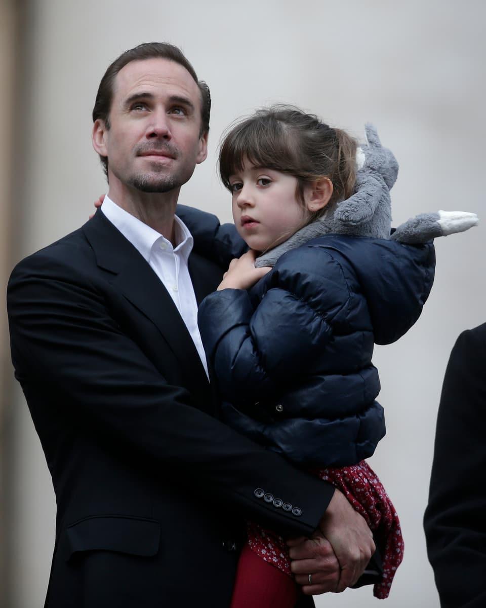 Joseph Fiennes hält seine Tochter im Arm und schaut beseelt in den Himmel.