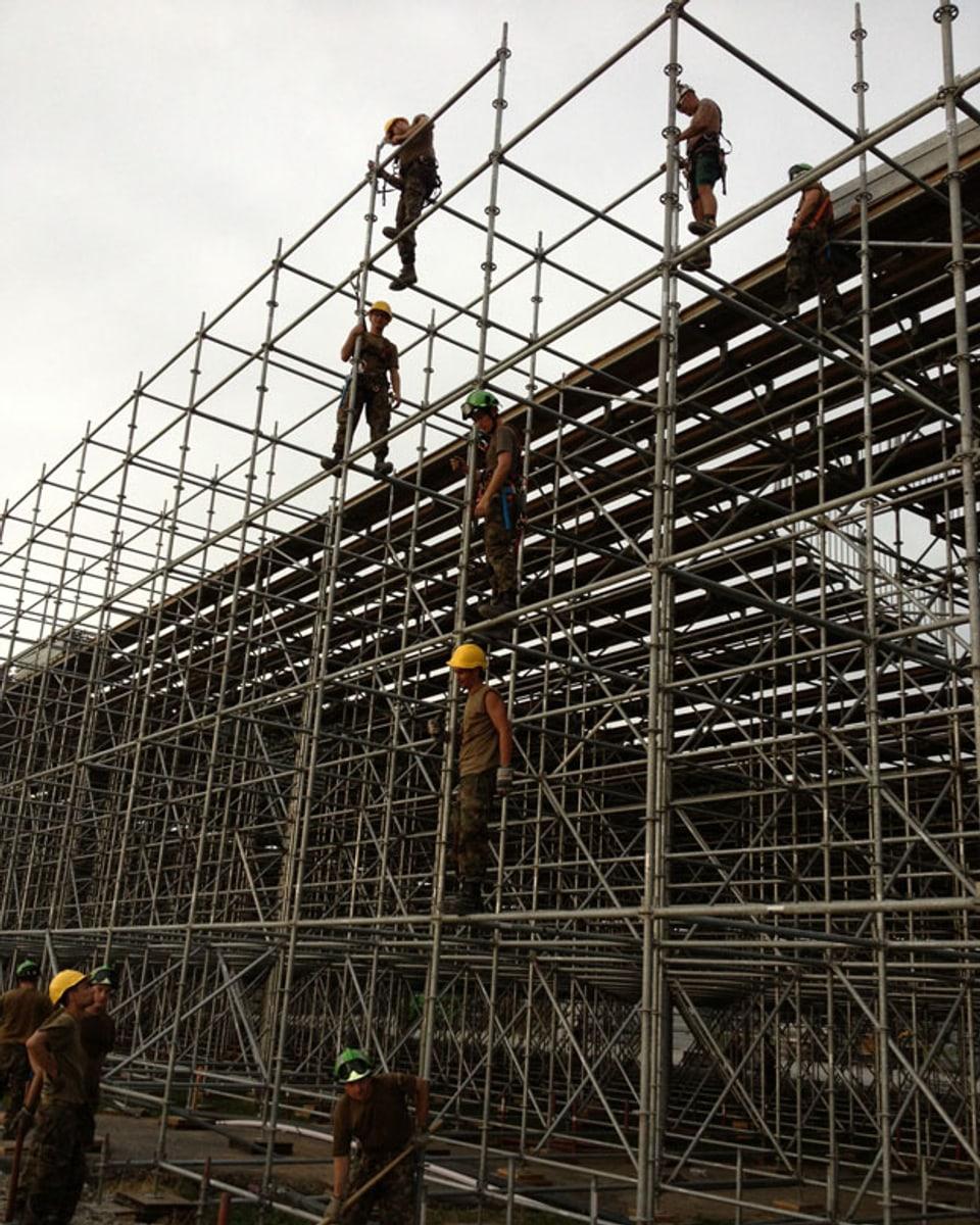 Männer vom Militär bauen die Tribühne auf.