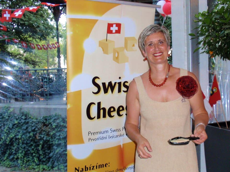 Barbara John vor einem «Swiss Cheese»-Plakat und mit einer Portion Raclette in Händen.
