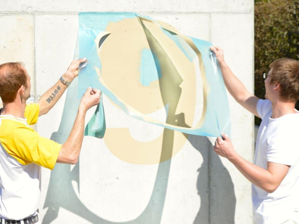 Zwei Maler lösen die Folie von der Wand.