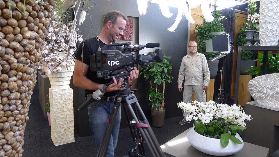 Der Kameramann trägt die Kamera mitsamt Stativ an die korrekte Stelle. Der Beleuchter kontrolliert die Lichtstimmung.