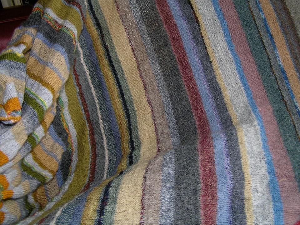 Detail einer angefangenen gestrickten Decke mit Streifenmuster in verhaltenen Farben aus feiner Fächtli-Wolle