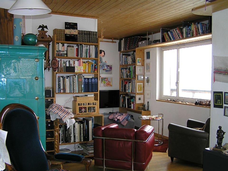 Wohnstube mit Kachelofen, mehreren Fauteuils, Bücherregal und Fenster