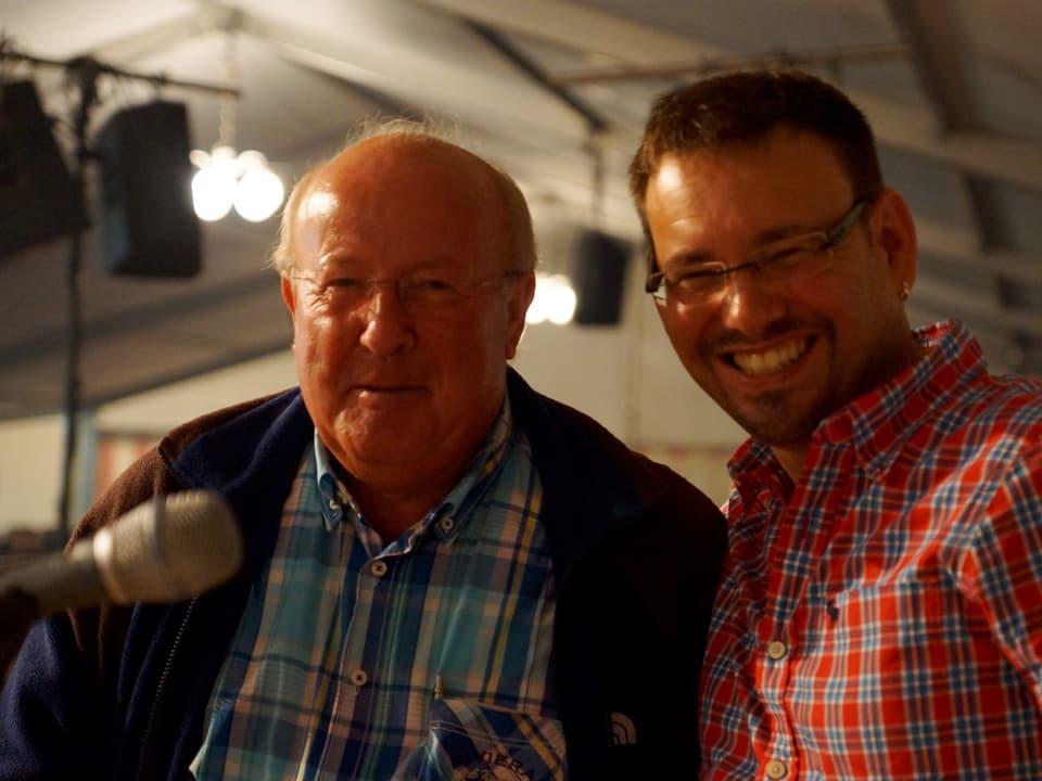 Kurt Stahl in blauer Kleidung und Guido Rüegge in roter lachen in die Kamera.