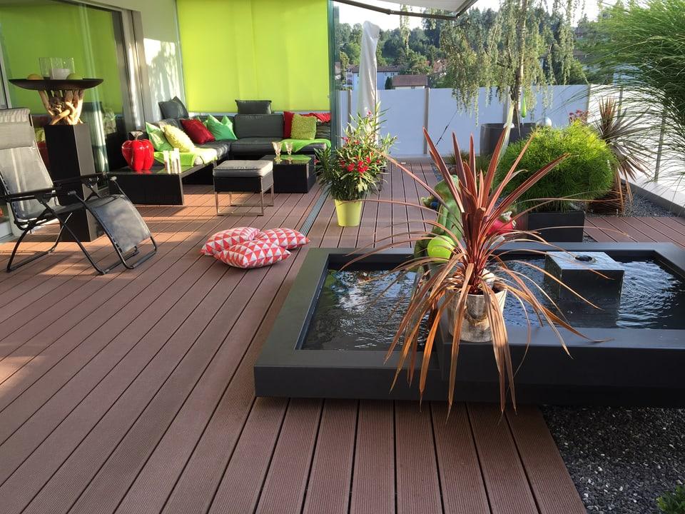 Terrasse mit rechteckigem Wasserbecken. Auf dem Holzbretterboden liegen Kissen und in einer Ecke stehen Loungemöbel.