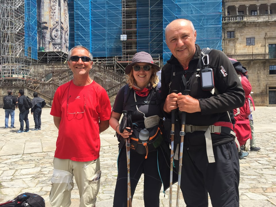 Ein Pilgertrio vor der Kathedrale in Santiago lacht in die Kamera