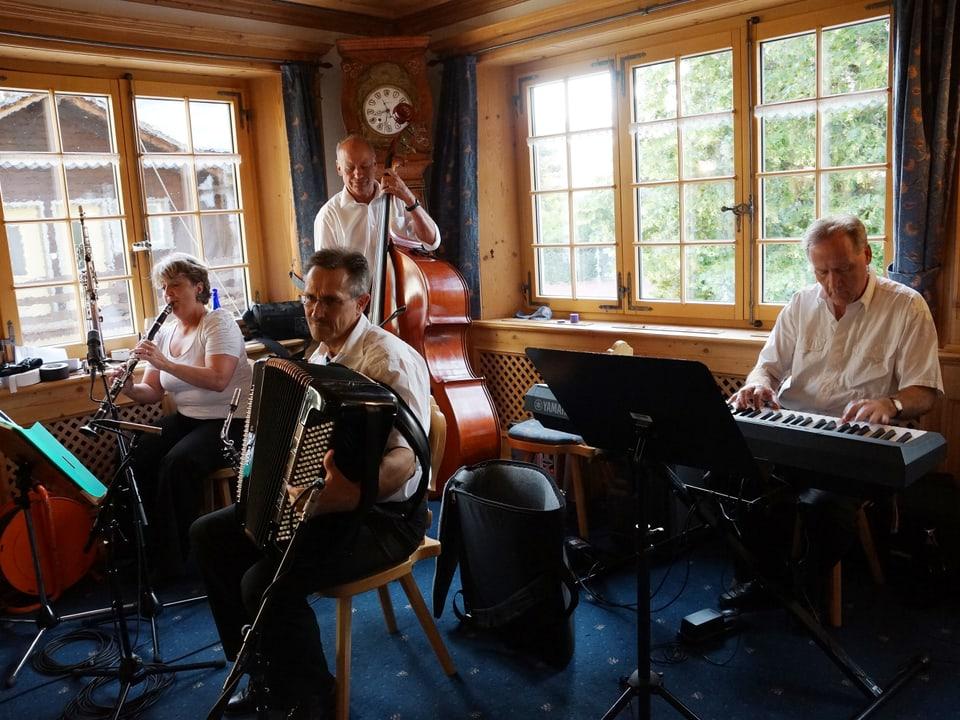 Eine Saxpophonistin, ein Bassgeiger, ein Akkordeonist und ein Pianist beim Musizieren in der Gaststube.