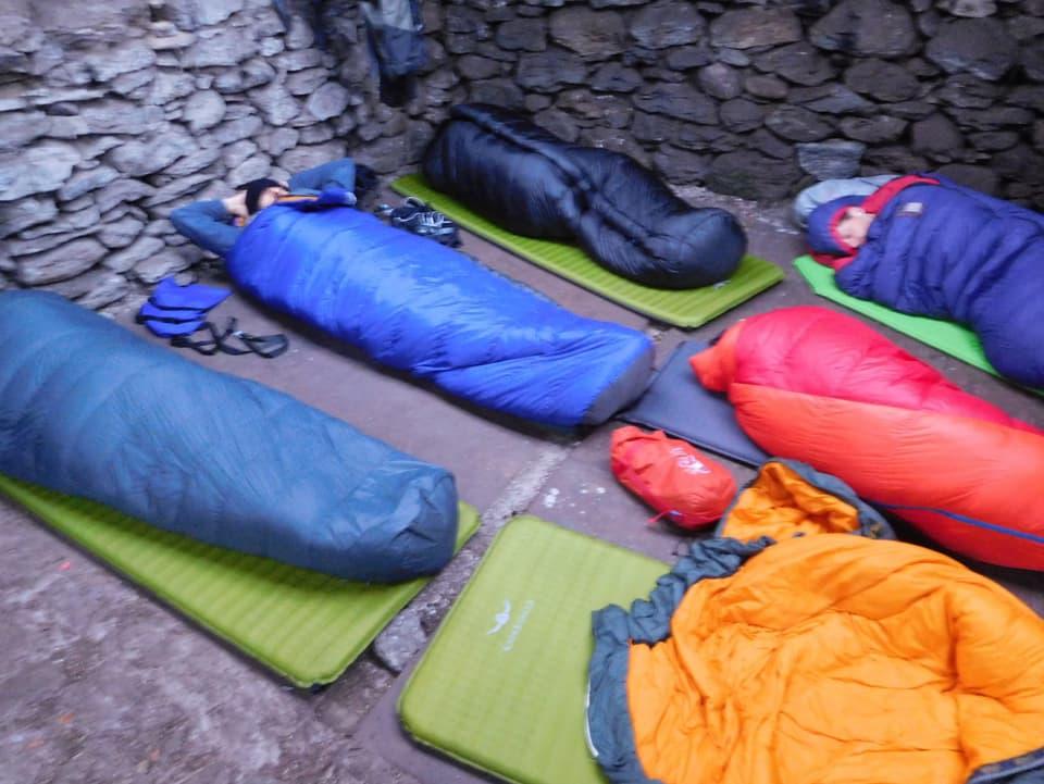 Schlafsäcke liegen auf dem Boden in unbewarteter Schutzhütte.